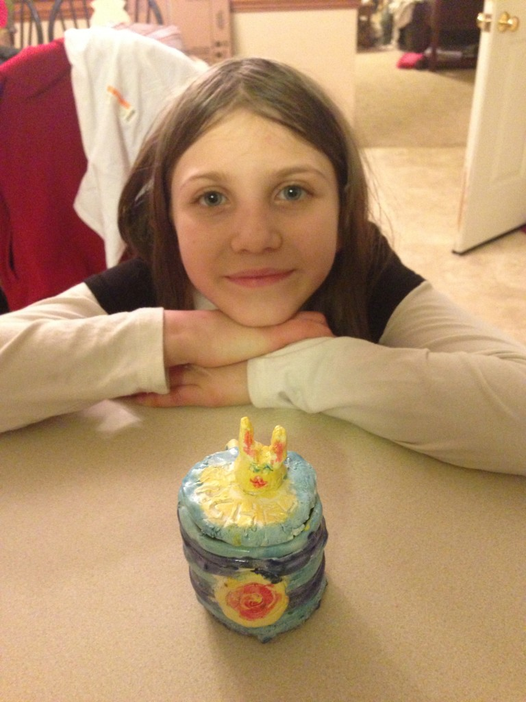 photo of Rachel behind her ceramic art project with a mug that has a bunny sculptured cover. The mug is multi-colored with blues yellow, and rose, and the bunny is mostly yellow.